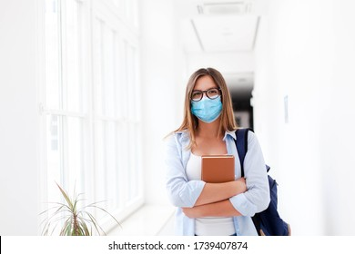 Student in protective face mask in empty college indoors. Young woman going to exams in high school. Girl with backpack and book in university corridor. Social distancing during quarantine.