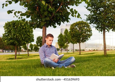 Student read a book sitting in the park under a tree on the grass