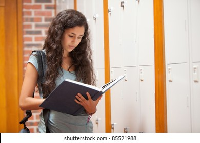 Student reading a book in a corridor