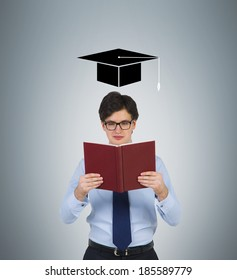Student reading the book and graduation hat