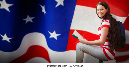 Student reading book in library against american flag with stripes and stars