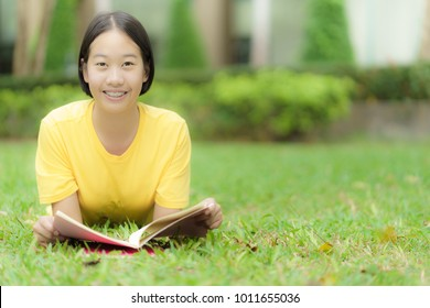 Student reading a book in park
