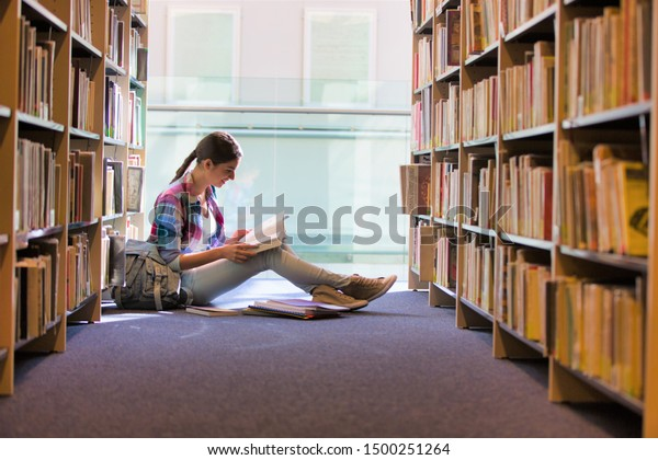 Student reading book while sitting against bookshelf at library