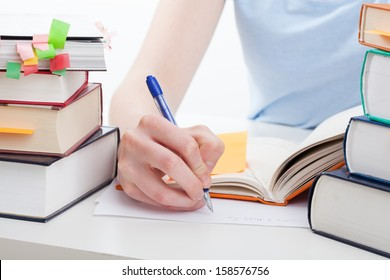 Student reading a book and writing the notes
