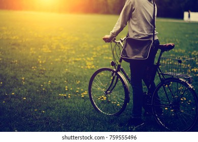 Student with a retro bike in sunset