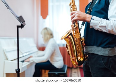 Student saxophone at a lesson in a music school close-up on the background of a teacher at the piano