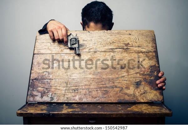 Student at school desk with gun