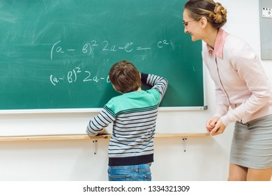 Student in school doing exercise at the blackboard writing equations