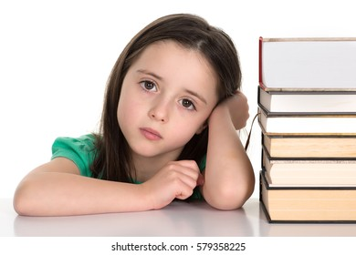 Student or a school girl sitting by the pile of books getting ready to do a homework. Isolated on a white background.