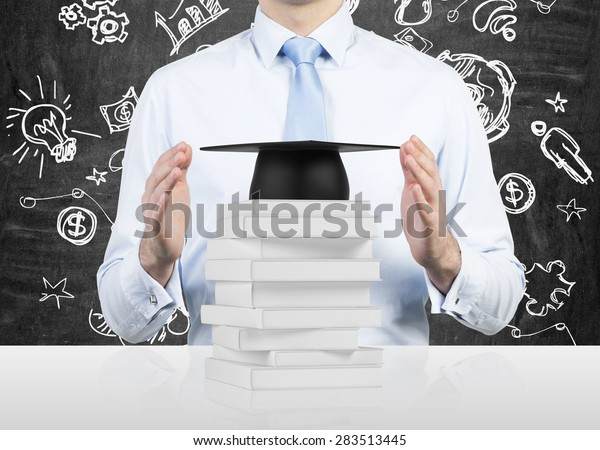 Student is securing books and a graduation hat. A concept of the privilege of the university degree. Educational icon on the background.