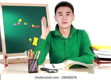 Student setting by a desk in the front of the blackboard