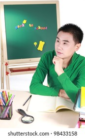 Student setting by a desk in the front of the blackboard.