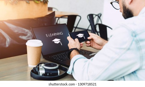 Student sits in cafe at table in front of laptop, using smartphone with inscription - e-learning and picture of square academic cap. Student learning online. Guy watching webinar.Online training.