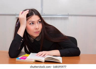 Student sitting in a classroom with books