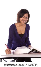 A student sitting at a desk smiling while taking notes from a book.