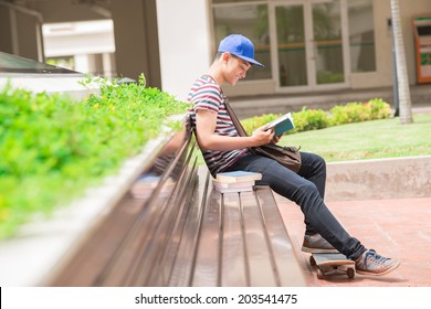 Student sitting on the bench and reading a book, side view