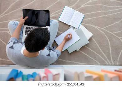 Student sitting on the floor with a laptop and doing homework, view from above