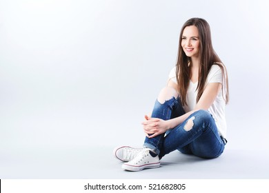 Student sitting in the studio. Young girl with straight long hair sitting on the floor.