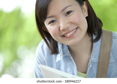 A student smiling surrounded by nature,