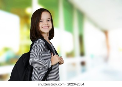 Student standing with a backpack at their school