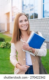 Student standing with books in her hands and smiling at camera on the sunset