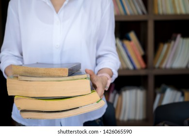 student standing in library holding books on his arms. education concept