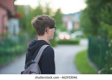 Student standing outside and wearing his school bag on one shoulder.