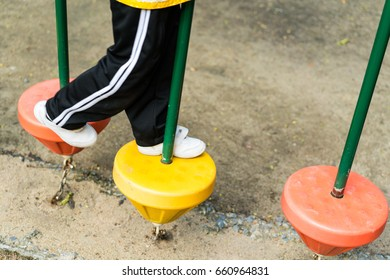 Student stepping on playground equipment in public park