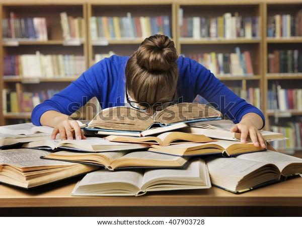厳しい試験と本で寝る学生、疲れた女の子が図書館で難しい本を読む