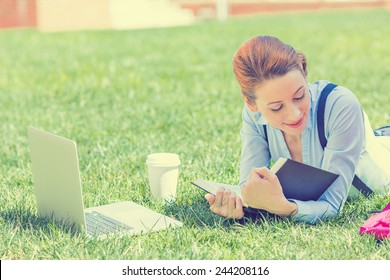 Student studying in park. Joyful happy young girl student sitting reading book outside on university campus or park. Education concept. Positive face expression