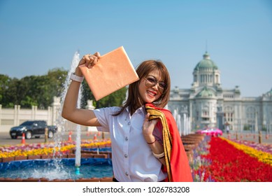 Student  take a picture outdoor fashion portraits in red graduation gowns on Beautiful garden,Concept - Congratulations  graduation.