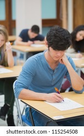 Student taking exam in exam hall in college