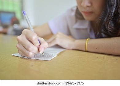 Student taking examination or writing test in the classroom. Educational and business concept image in selective focused style of a girl sitting and studying in a learning room