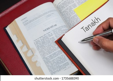 A student of Tanakh writing on a notebook with a bible opened to the book of the prophet Nehemiah.