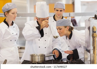 Student tasting the teacher's soup in culinary school
