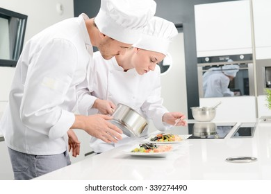 student and teacher in a professional cook school kitchen preparing a plate for restaurant
