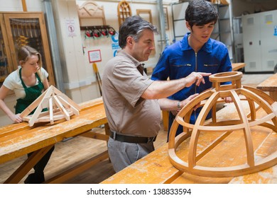 Student and teacher standing in a woodwork class and working on a structure