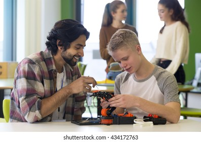Student and teacher working on a robotic arm in a classroom. There are students standing in the background.