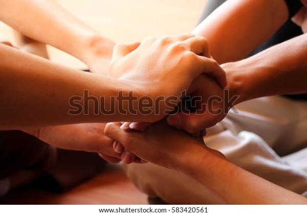 student team siting hands together under sunshine