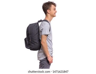 Student teen boy with backpack - side view. Portrait of cute smiling schoolboy with hands in pockets, isolated on white background. Happy child Back to school - profile.