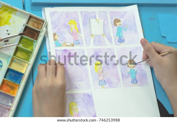 Student teenage girl hands drawing cartoon in watercolor about her teen life on blue table.