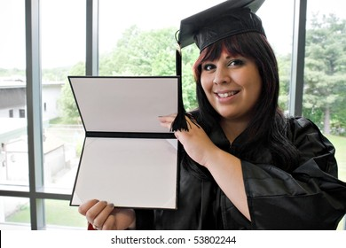 A student that recently had a school graduation posing proudly with her diploma indoors.