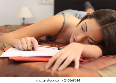 Student tired and sleeping in her bed room over the notes while was studying