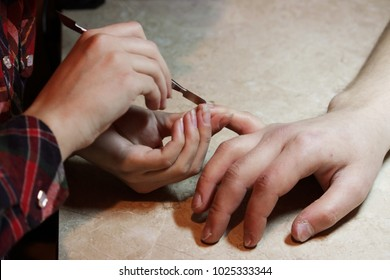A student at the training courses of a manicure gives shape to nails the hand of a man client with a for removing superfluous cuticles and pterygium