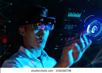 Student trying vr glasses hololens in the dark room. Young asian boy experiences ar with control panel like iron man.
