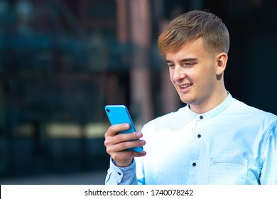Student Types a Message, a handsome European man texting a message, sms on his mobile smartphone. Cheerful young, businessman man, looks at his cell phone, reading, surfing  makes a video call.