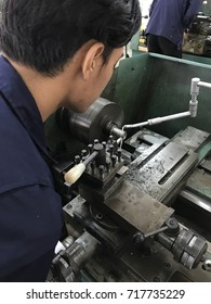A student use a lathe machine