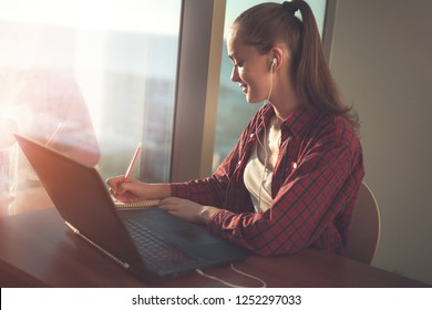 Student using online education service. Young woman looking in laptop display watching training foreign language courses and taking notes in notebook. Modern study technology concept.