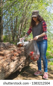 A student volunteer cleans a forest area from garbage.The concept of volunteerism and environmental protection.