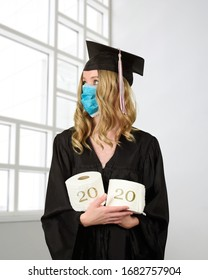 A student is wearing a graduation cape and robe holding toilet paper for a humorous concept of the class of 2020 coronavirus pandemic of the covid-10 shutdown.